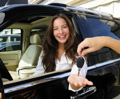 Businesswoman Receiving Keys Of Her New Car From Dealer